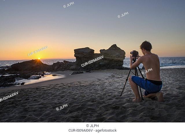 Teenage boy taking photos, Table Rock Beach, Laguna Beach, California, USA