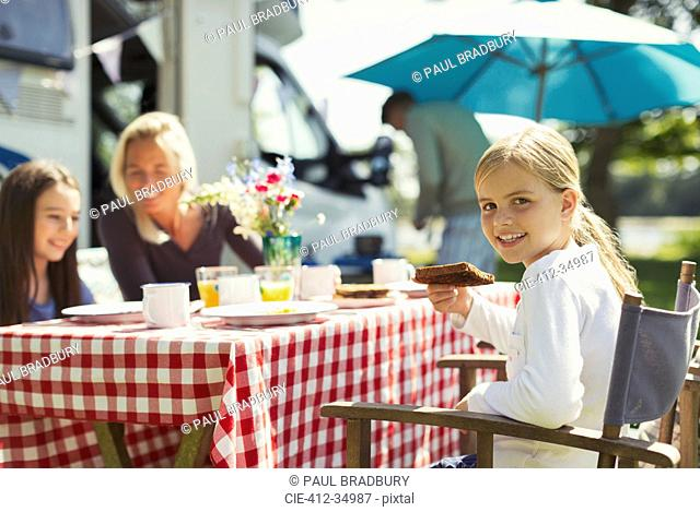 Portrait smiling girl eating breakfast with family outside sunny motor home