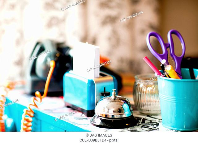 Stationery and service bell on reception desk of quirky hair salon
