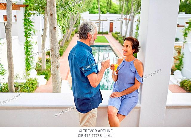 Mature couple drinking mimosas on hotel balcony