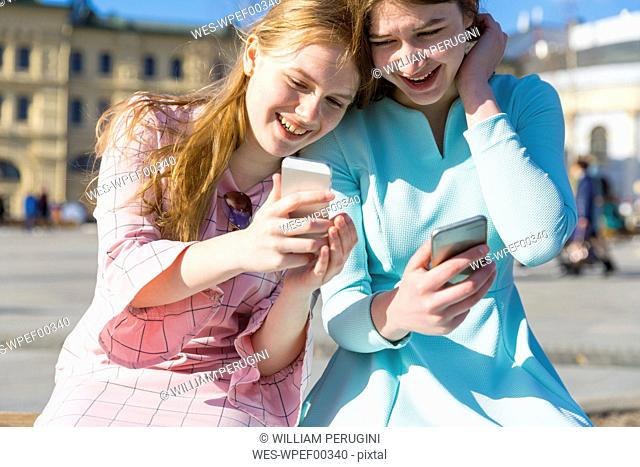 Russia, Moscow, teenage girls with smartphones in the city