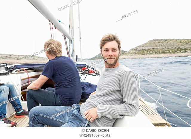 Young man on yacht looking out to sea