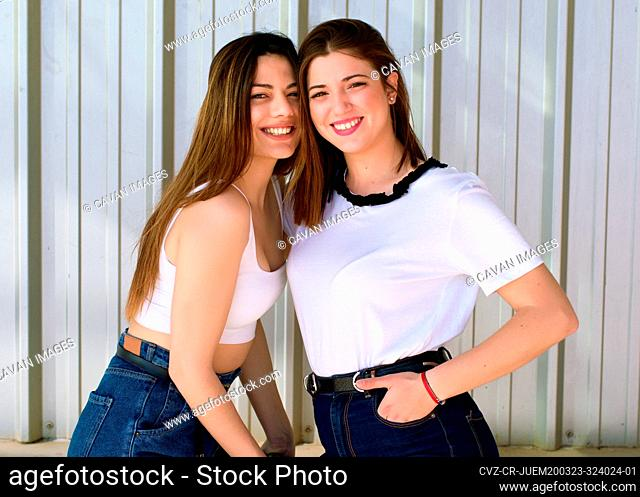 two young friends hug and laugh happily looking at the camera