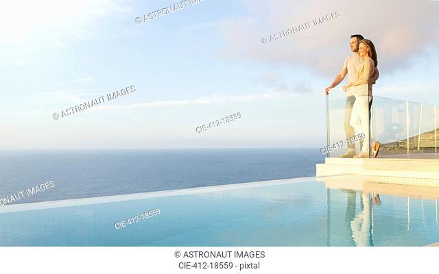 Couple overlooking ocean from modern balcony