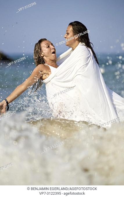 between water splashes, waves, two women shrouded in white blanket sheet, standing in sea, best friends, holidays. Chersonissos, Crete, Greece