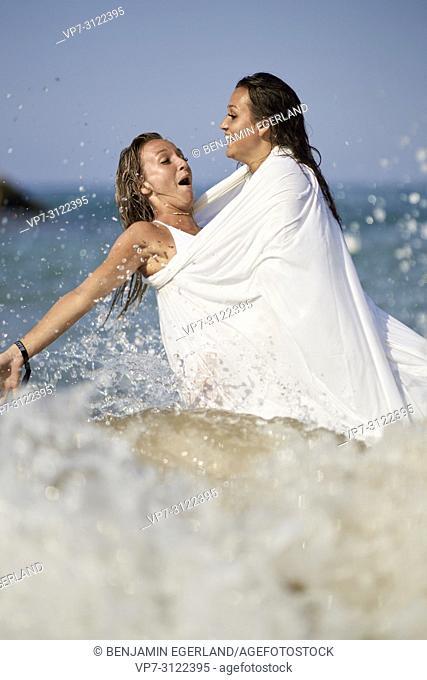 between water splashes, waves, two women shrouded in white blanket sheet, standing in sea, best friends, holidays. Chersonissos, Crete, Greece