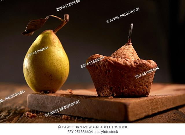 Sweet muffins with pears on the wooden plank