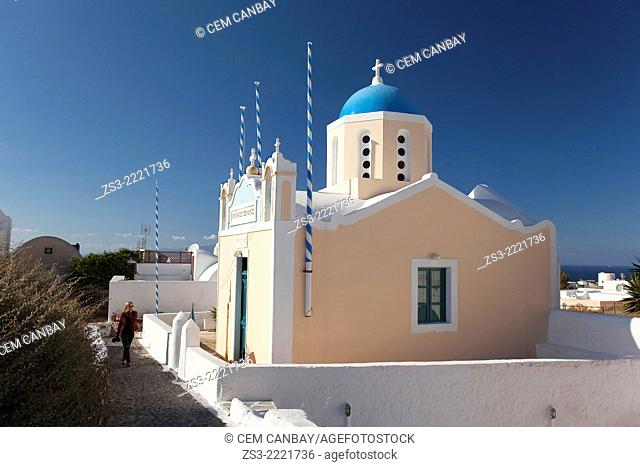 Woman in front of a blue domed church, Oia, Santorini, Cycldes Islands, Greek Islands, Greece, Europe