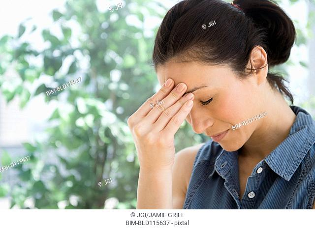 Caucasian woman rubbing her forehead