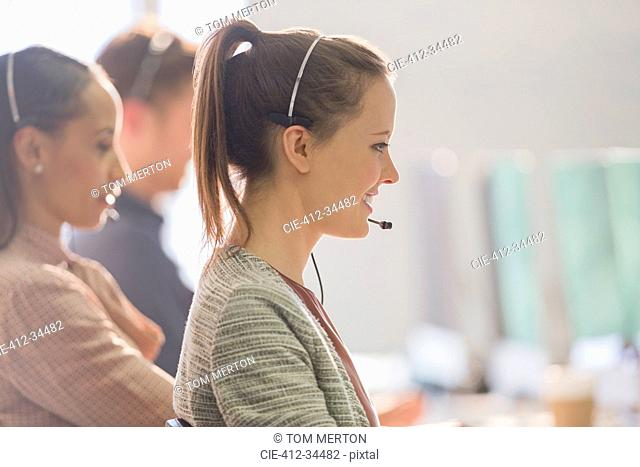 Smiling female telemarketer wearing headset talking on telephone in office