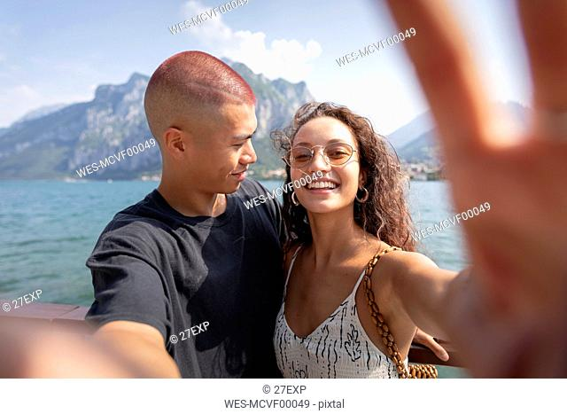Young couple taking selfie in front of Lake Como, Lecco, Italy