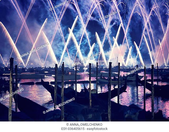 Redentore holiday, Redeemer festival of fireworks, people in gondolas swimming along canal and enjoying majestic salute in the sky, Venice, Italy
