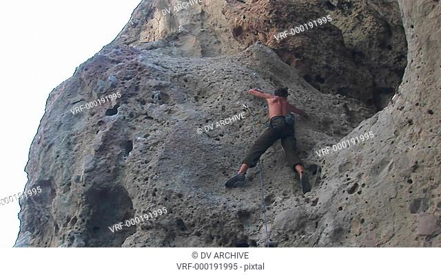 Pan-right of a rock climber scaling a cliff wall