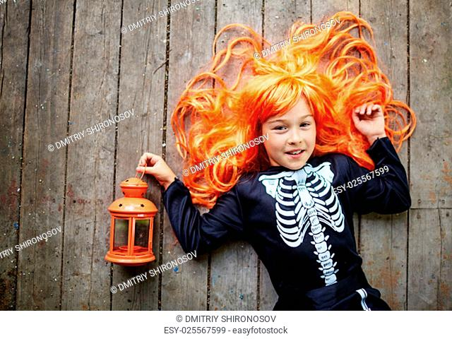 Happy girl in orange wig and Halloween attire looking at camera while lying on wooden floor