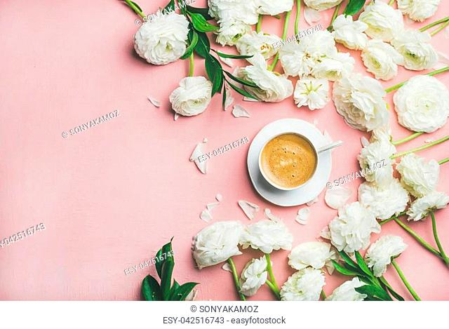 Spring morning concept. Flat-lay of cup of coffee surrounded with white ranunculus flowers over light pink background, top view, copy space