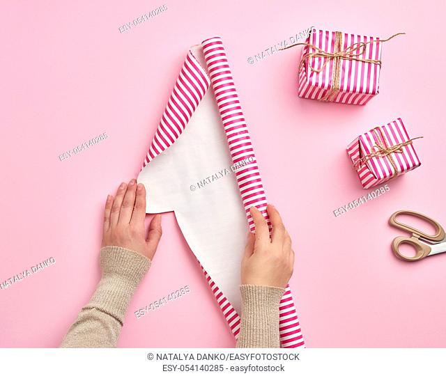 two female hands unfold a roll of wrapping paper, next to two gifts, pink background, preparing surprises