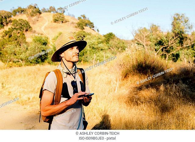 Hiker holding smartphone looking away, Malibu Canyon, California, USA