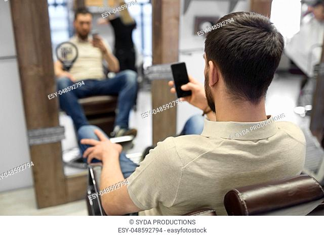 man with smartphone at barbershop or hair salon