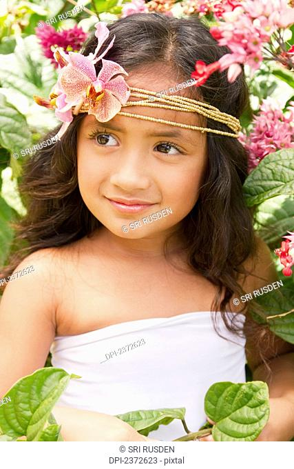 Portrait of a young girl with tropical flowers in her hair; Honolulu, Hawaii, United States of America