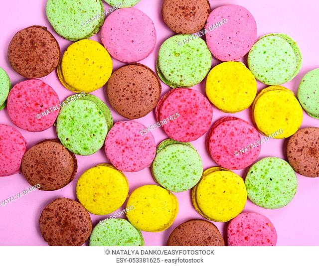 Colorful pastry macarons on a pink background