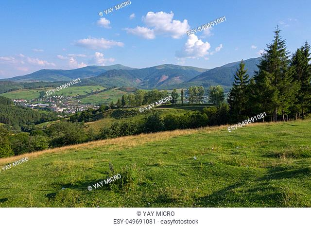 Magnificent landscape of mountain slopes and peaks standing in the distance against the background of the blue sky and lying city of the valley