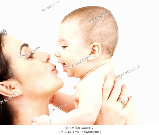 family, parenting and child care concept - happy mother kissing adorable baby