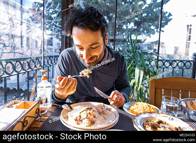 handsome man smiles while eating his meal on plate in a restaurant in quarantine days