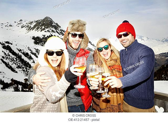 Couples celebrating with drinks in the snow