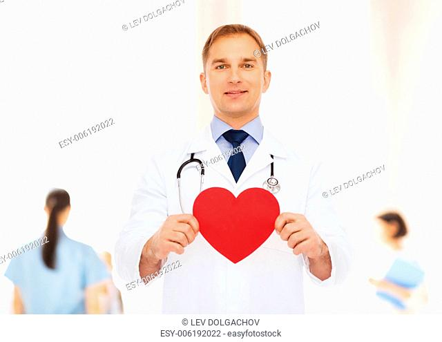 medicine, profession, charity and healthcare concept - smiling male doctor with red heart and stethoscope over group of medics