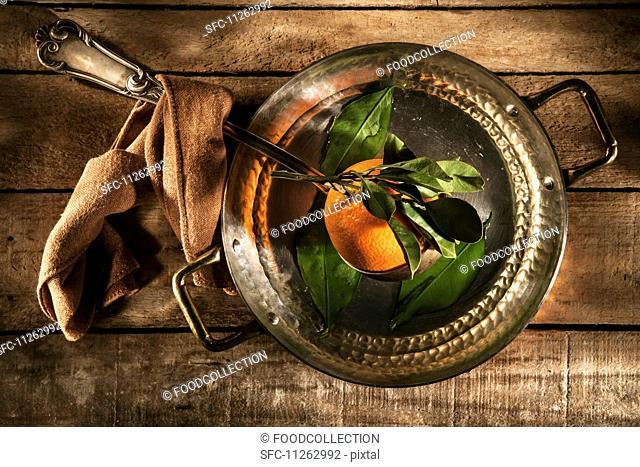 A freshly picked orange in a copper saucepan