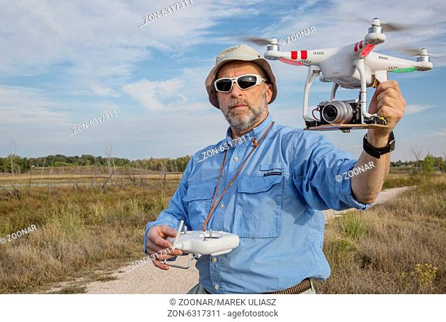 FORT COLLINS, CO, SEPTEMBER 28, 2014: Photogrpaher, Marek Uliasz, is launching the DJI Phantom 2 quadcopter drone with Panasonic Lumix GM1 camera on board