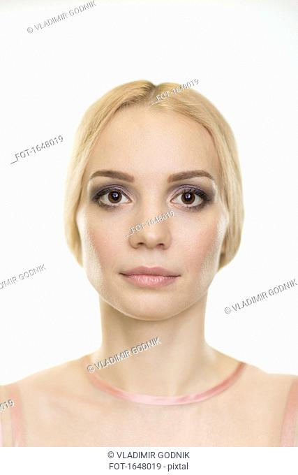 Portrait of beautiful woman with make-up and blond hair against white background