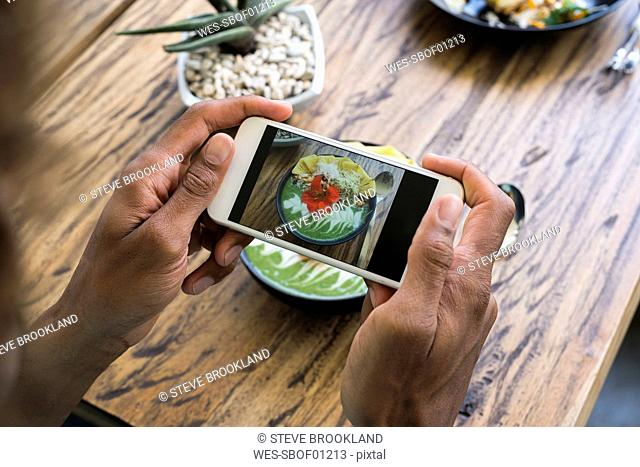 Male hands taking a picture of smoothie bowl with smartphone