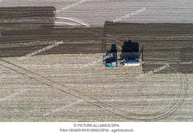 09 April 2018, Germany, Sieversdorf: Fermentation residues from a biogas plant are spread on a field (taken with drone). The residues which remain after the...