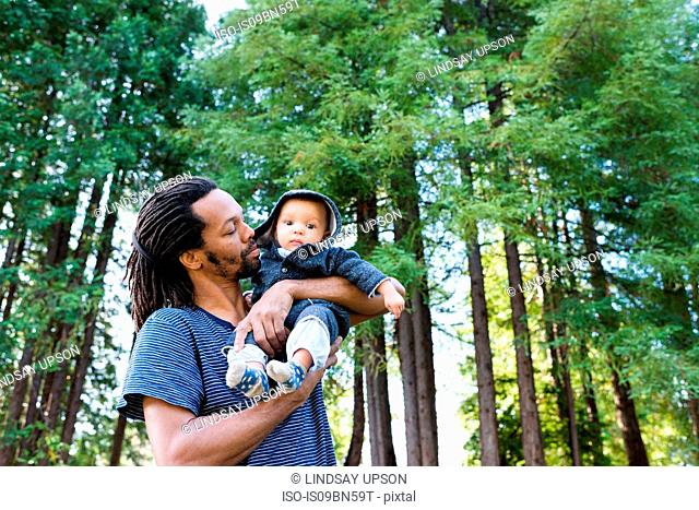 Mature man in forest carrying baby son in arms