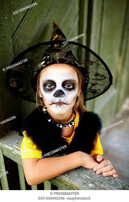 Sullen girl in Halloween costume looking at camera