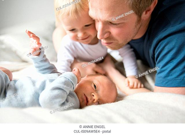 Father and big brother looking down at baby boy smiling