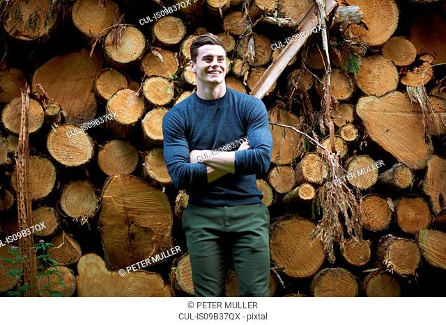 Portrait of man in front of tree trunks