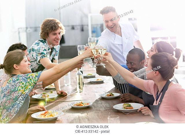 Chef teacher and students toasting wine glasses in cooking class kitchen