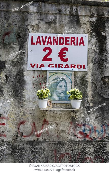 Sacred and profane, Image of Jesus and advertisement for laundrette on a tattered wall, Spanish Quarter, Naples, Italy