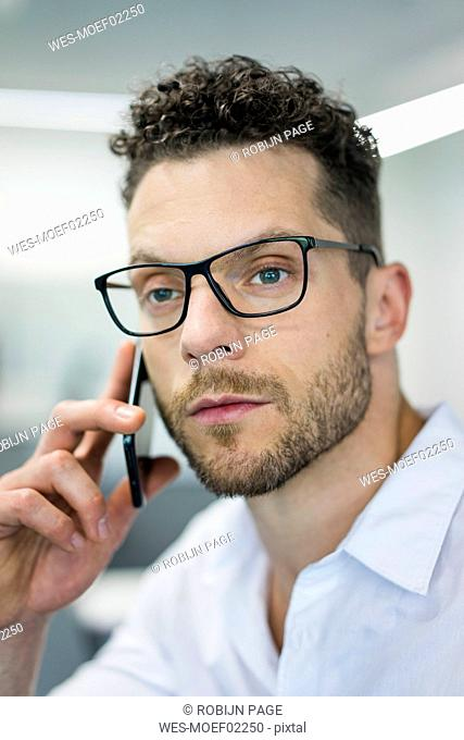 Portrait of businessman on cell phone in office