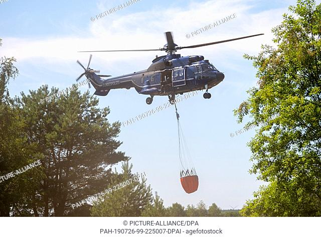 26 July 2019, Brandenburg, Jüterbog: A fire-fighting helicopter of the Federal Police is in action in a forest fire at a former military training area near...