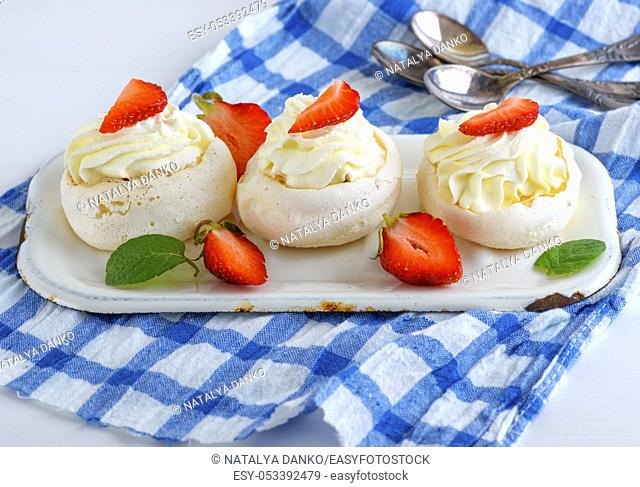 round baked meringue pie with strawberries on a blue textile napkin, close up