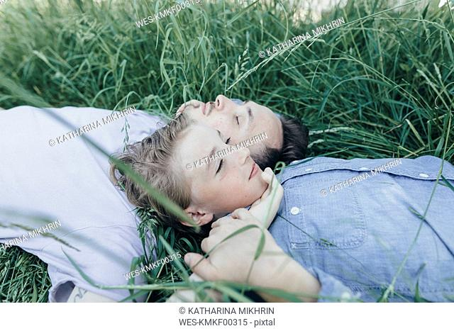 Young man and boy lying in field
