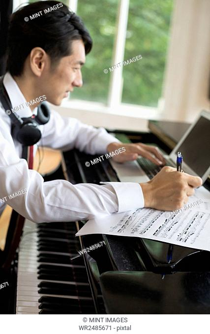 Young man sitting at a grand piano in a rehearsal studio, annotating sheet music