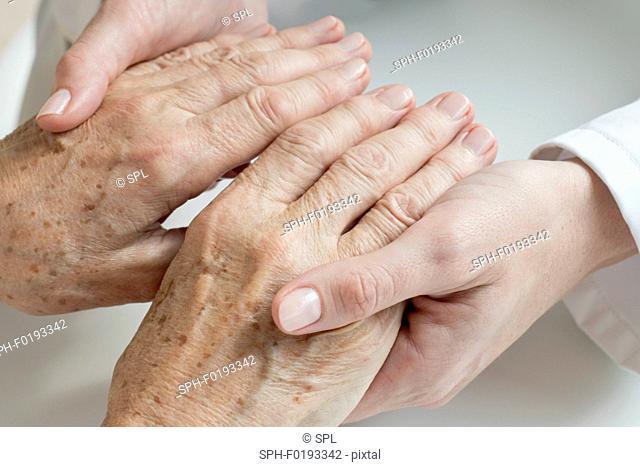 Female doctor examining senior patient's hands