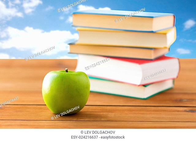 education, school, literature, reading and knowledge concept - close up of books and green apple on wooden table over blue sky and clouds background