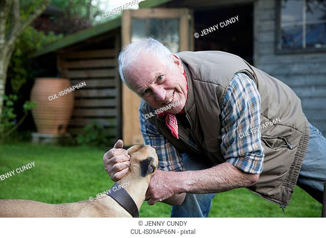 Senior man, stroking pet dog in garden