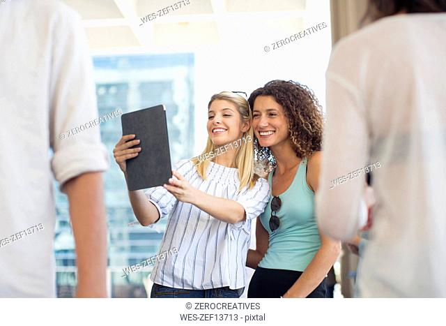 Two happy women taking a selfie with tablet on urban square
