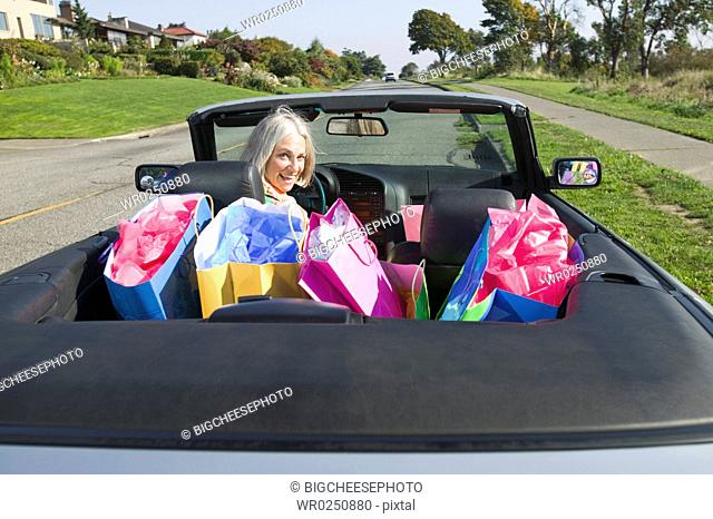 Woman with shopping bags in convertible